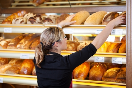 bakery shop: young woman taking bread from shelf in bakery