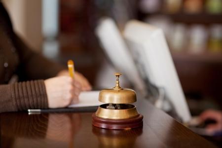 vestibulos: campana en el mostrador del hotel con la mujer llenando un Formulario Foto de archivo