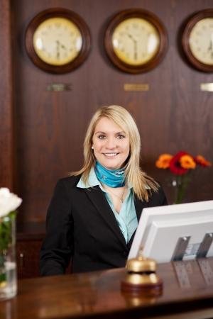lachende blonde receptioniste achter de balie in het hotel Stockfoto