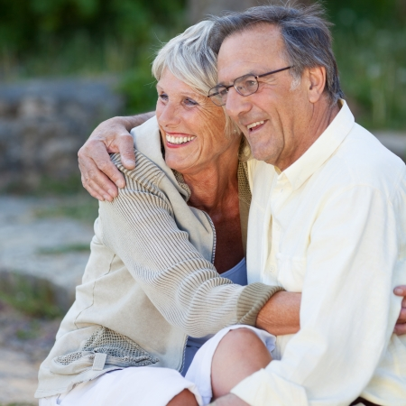 lovers park: Happy loving senior couple looking away while embracing in park Stock Photo