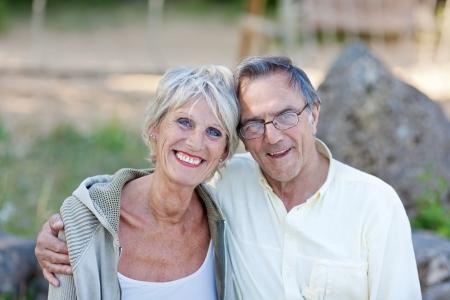 Portrait of happy loving senior couple smiling in park photo