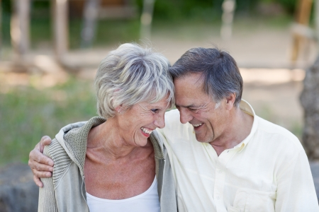 Happy loving senior couple with head to head smiling in park photo