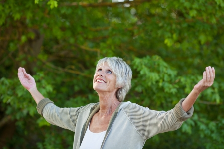 woman arms up: Happy senior woman with arms outstretched in park Stock Photo