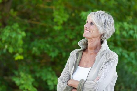 Glückliche ältere Frau, die an den schönen Bäumen Standard-Bild