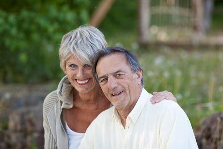 looking around: Portrait of happy senior couple smiling in park