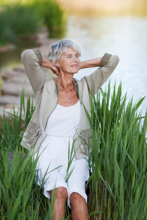 Happy senior woman with hands behind head relaxing by lakeside in park photo