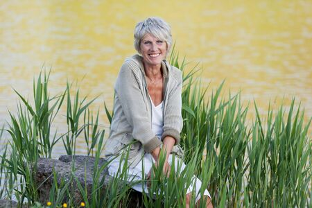 Happy and cheerful old lady sitting near the lake and enjoying the views. photo