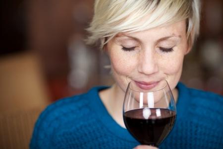눈으로 레드 와인을 마시는 젊은 여성 고객의 근접 촬영 초상화 폐쇄