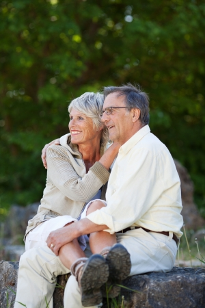 60s adult: Happy romantic senior couple looking away while embracing in park