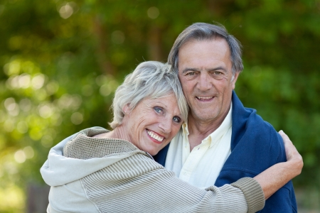 Senior woman hugging her male partner outdoors, a sweet elderly couple in love.