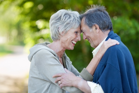 head shot: Profile shot of happy loving senior couple with head to head smiling in park Stock Photo