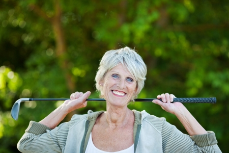 Cheerful happy older woman with a golf stick in the golf club. photo