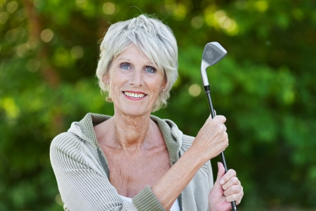 Happy old lady holding the golf stick standing in the golf club. photo
