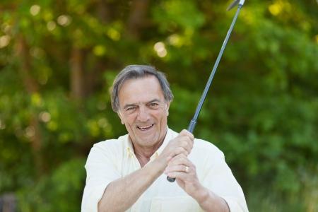 Portrait of happy senior man playing golf in park photo