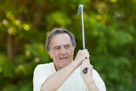 Elderly man with golf stick in action inside the golf club. photo
