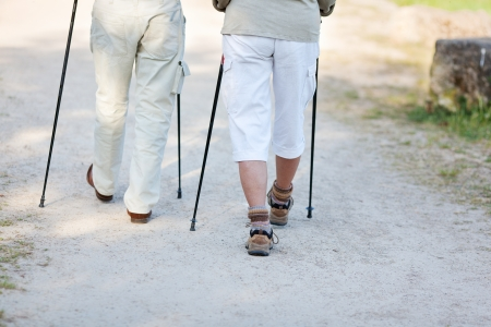 trekking pole: Elderly couple traveling with nordic walking sticks, walking together.