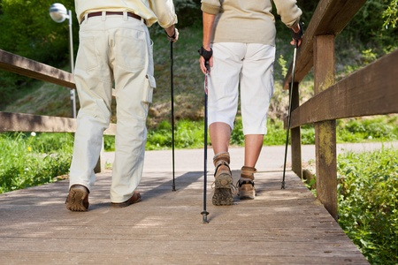 Senior couple walking on the bridge with the help of nordic sticks.