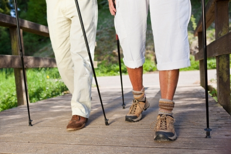 guy with walking stick: Low section of senior couple walking on boardwalk while hiking in forest