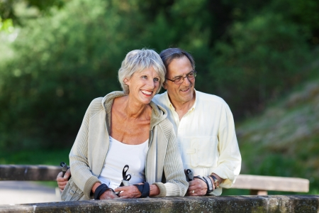 nordic walking: Happy senior couple looking away while hiking in forest