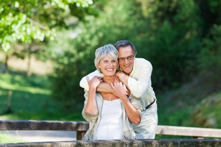 old couple: Happy senior man embracing wife from behind while looking away in park