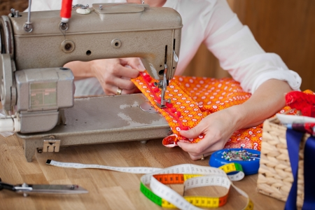 Seamstress with her sewing machine sewing a border onto a colourful orange item of clothing as she works at her table