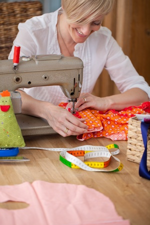Female fashion designer sewing clothes in workshop photo