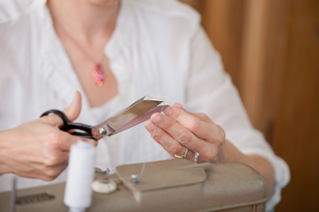 Cropped image of female fashion designer cutting thread with scissors in workshop photo