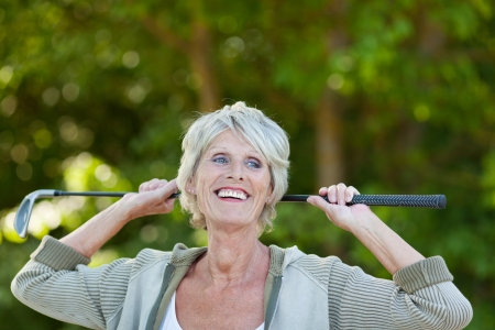 Happy senior woman holding golf club while looking away in park Stock Photo - 21258997
