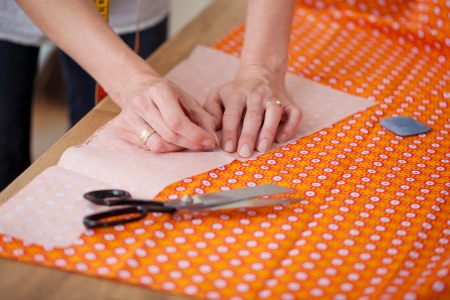 attaching: Closeup of fashion designers hands attaching pin to cloth in workshop Stock Photo