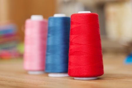 upright row: Rolls of colourful sewing thread or yarn standing upright in an oblique row on a wooden counter top with shallow dof Stock Photo