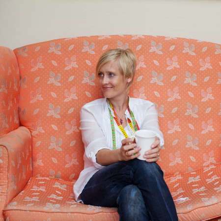 Female fashion designer holding coffee mug while looking away on sofa photo