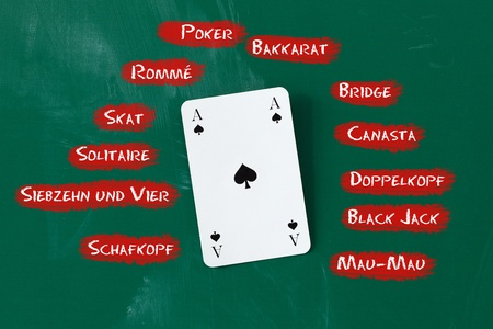 skat: Closeup of ace card surrounded by game names on blackboard