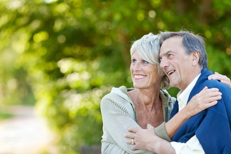 Cute elderly couple holding each other and laughing while looking at something. photo