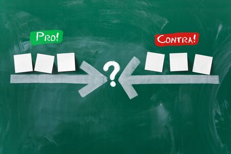 Closeup of arrows pointing at question mark with sticky notes on blackboard representing pros and cons photo