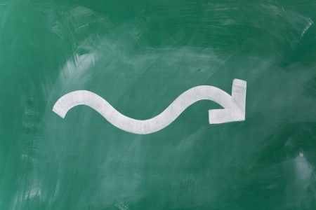 Closeup of wavy arrow drawn on blackboard representing fluctuation in business photo