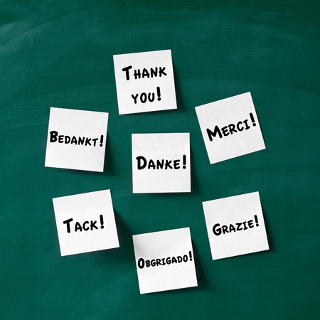acknowledgment: Closeup of sticky notes with Thank You written in various languages stuck on blackboard