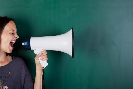 Vrouw schreeuwen in megafoon in de voorkant van een schoolbord