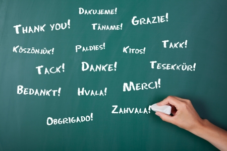 Closeup of woman's hand writing Thank You in various languages on chalkboard Stock Photo - 21230263