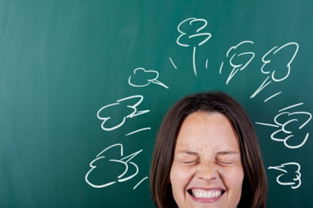 clenching: Closeup of angry woman with eyes closed clenching teeth against chalkboard Stock Photo