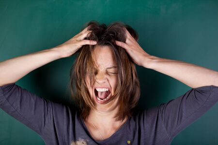 greenboard: Closeup of frustrated woman with hands in hair screaming against chalkboard
