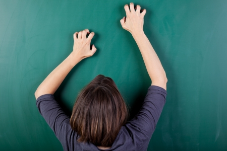 aggressive people: Closeup rear view of frustrated woman scratching chalkboard