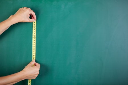 Closeup of womans hands measuring blackboard with tape Stock Photo
