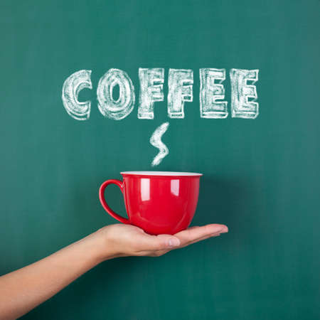 Closeup of womans hand holding coffee cup with coffee written on chalkboard photo
