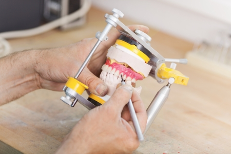 articulator: Closeup of male dental technicians hands working with articulator in dental laboratory Stock Photo