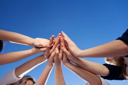 solidaridad: �ngulo de visi�n baja de las manos contra el cielo azul