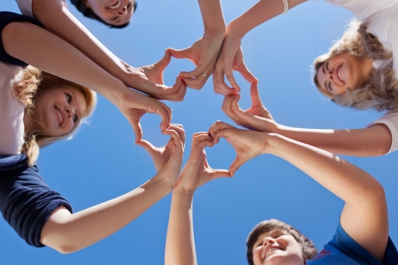 Low angle view of children and teacher forming hearts against clear blue sky Reklamní fotografie