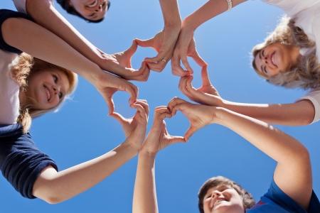 solidaridad: Ángulo de visión baja de los niños y la formación de maestros corazones contra el claro cielo azul