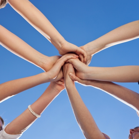 Teenagers showing unity and commitment all putting their hands to the centre of a circle against a sunny blue sky