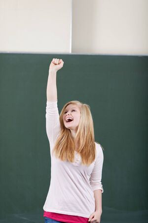 Young attractive young teenage girl student rejoicing by cheering and raising her arm in the air in front of the blackboard in the classroom photo