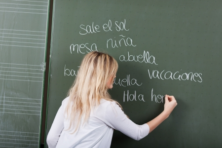 spanish girl: Rear view of teenage girl writing words on blackboard in classroom